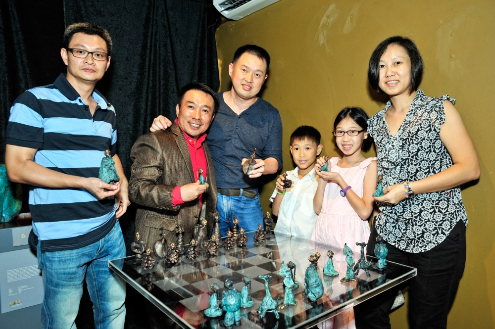 """Gallery owner Winson Loh, artist Ch'ng Huck Theng and guests, with Ch'ng's work: """"Checkmate"""""""